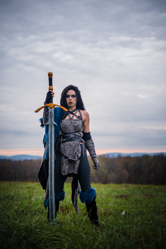 A woman dressed in a Critical Role Cosplay stands in a field with a giant sword at sunset