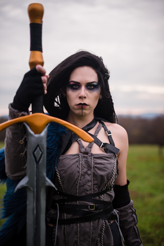 A woman dressed as Yasha from Critical Role stares at the camera in a field during sunset