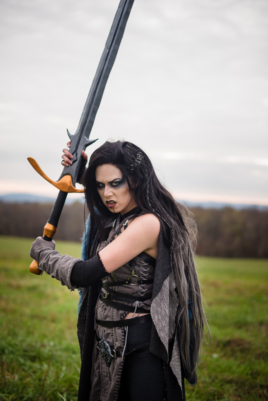 A woman dressed as Yasha from Critical Role gets ready to swing her sword