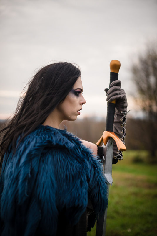 A woman dressed as Yasha from Critical Role has a tear trailing down her cheek while standing in a field