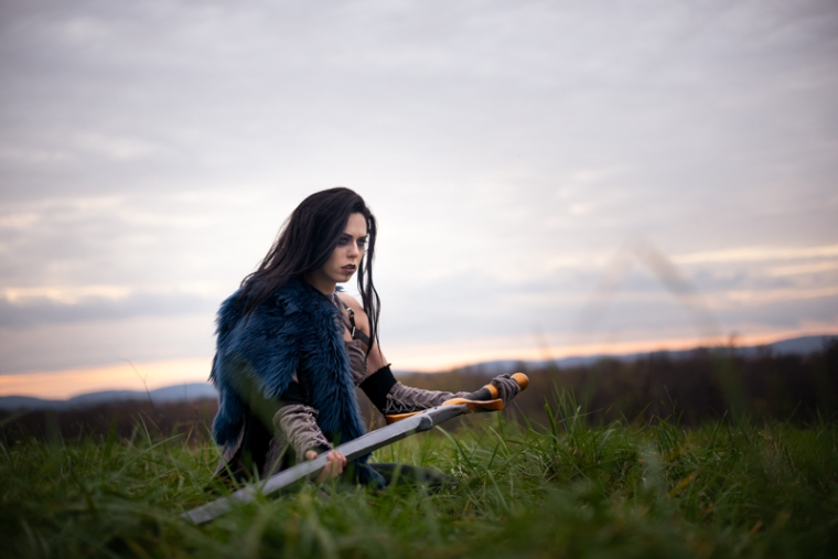 A woman dressed in a critical role cosplay kneels in a field with a sword during sunset