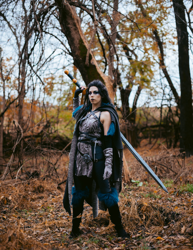 A woman dressed as Yasha from Critical Role reaches behind her to grab her giant sword
