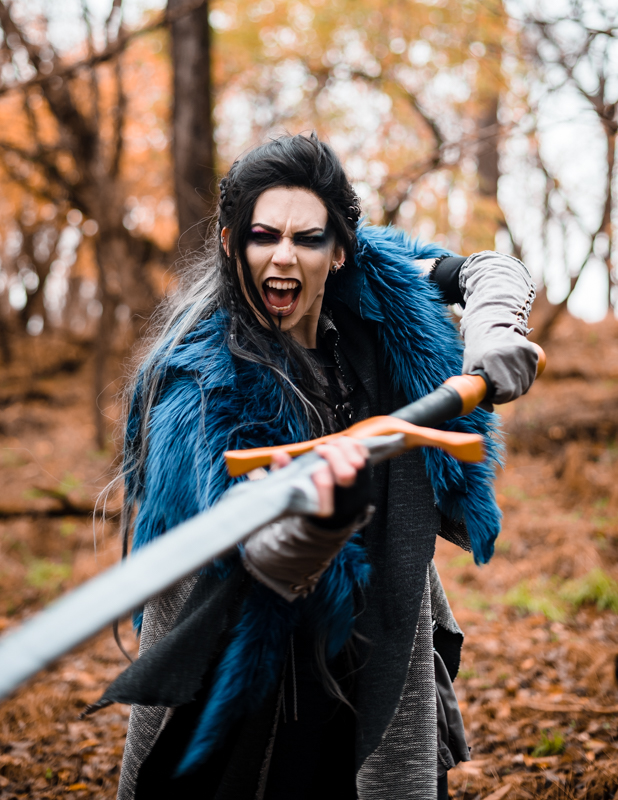 A woman dressed in a Critical Role Cosplay yells as she swings her giant sword