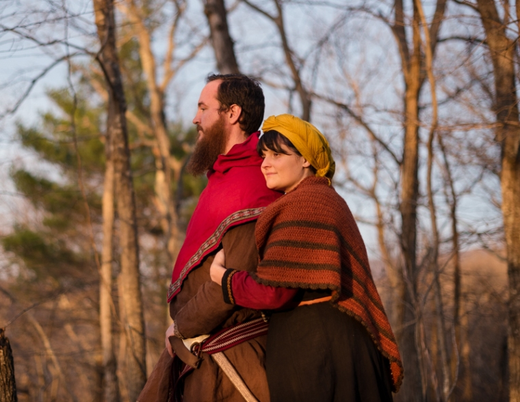 A viking larp couple stand together in the woods during sunset during their Harpers Ferry Engagement photos