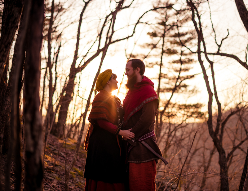 A viking larp couple is poses against the setting sun during their Harpers Ferry engagement photos