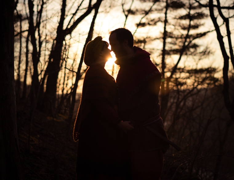 A viking larp couple is silhouetted against the setting sun during their Harpers Ferry engagement photos