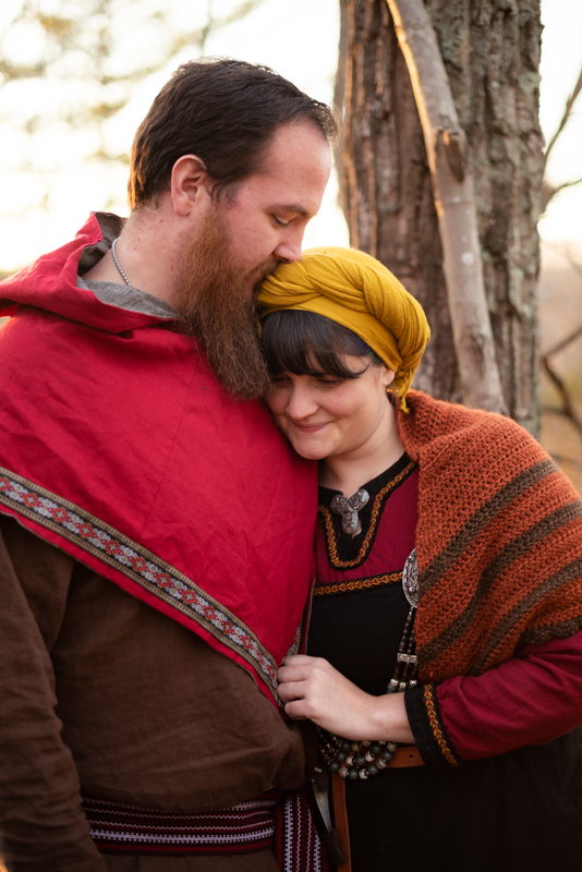 A man kisses his wife's forehead while dressed in viking larp garb during their Harpers Ferry engagement photos