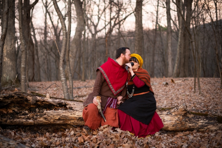 A viking larp couple sit on a tree in the woods drinking during their Harpers Ferry Engagement photos