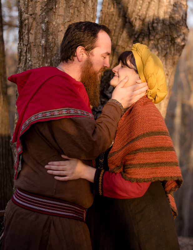 A man pulls his wife in for a kiss during their viking engagement photoshoot in Harpers Ferry