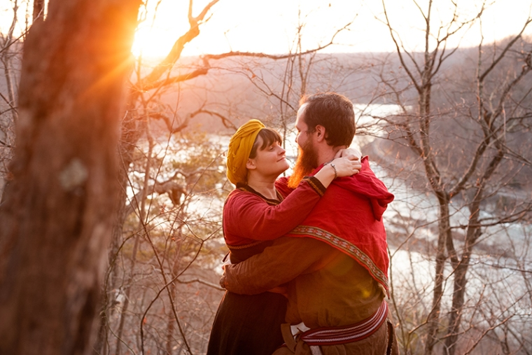 A couple gazes at each other with a river in background at sunset during their viking engagement shoot in Harpers Ferry