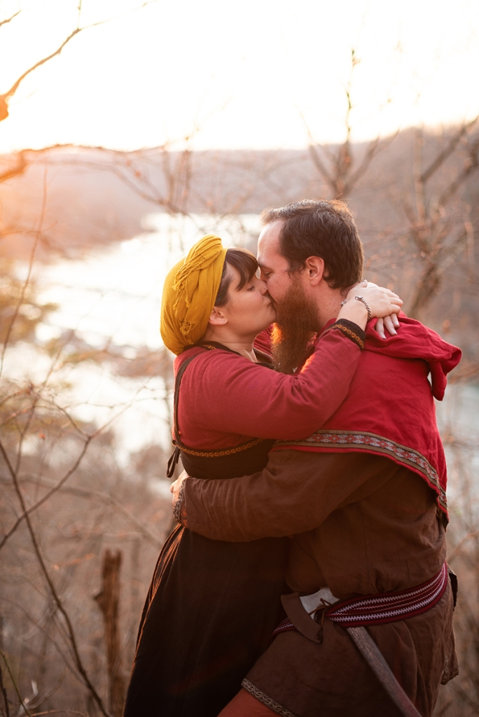 A couple kisses with a river in background at sunset during their viking engagement shoot in Harpers Ferry
