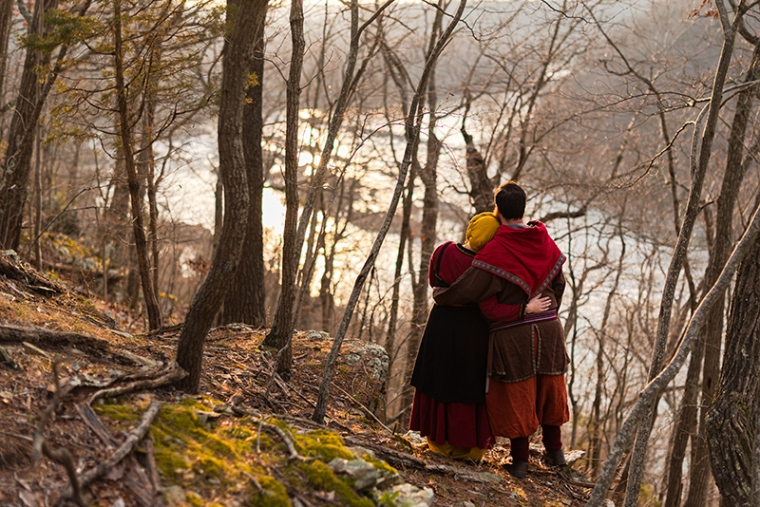 A viking larp couple looks at out over the river during their Harpers Ferry engagement photos