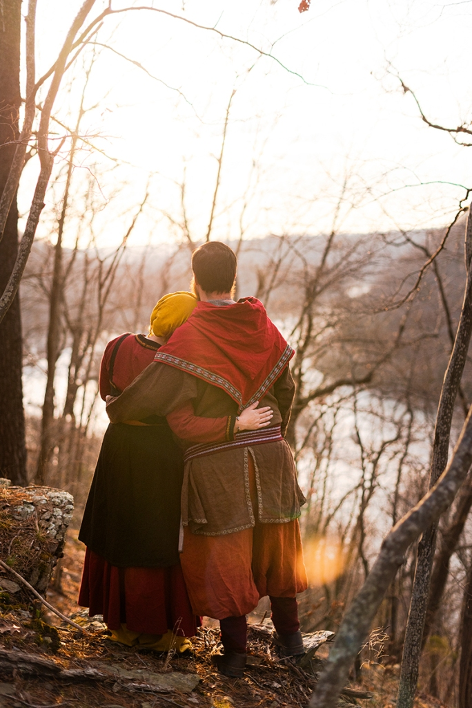 A viking larp couple stands looks out over a river during their Harpers Ferry Engagement Photos