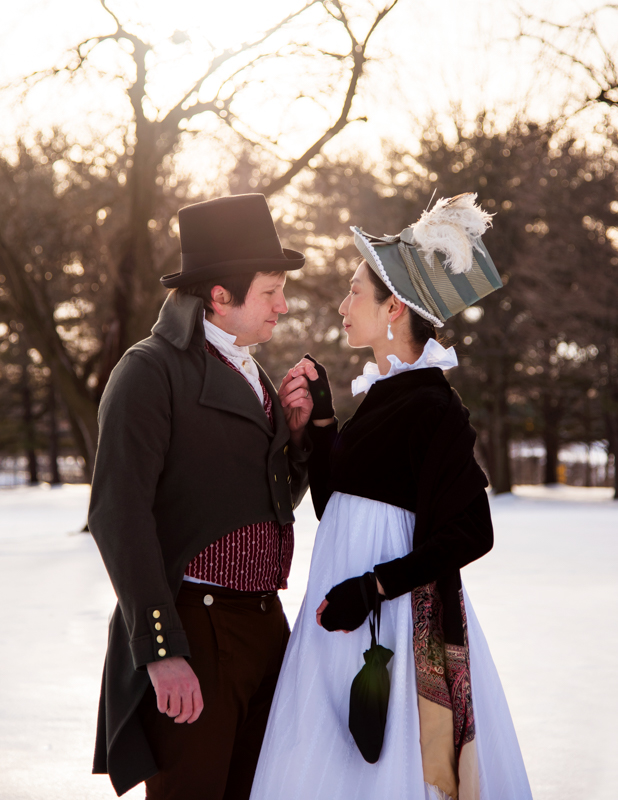 A man holds his wife's hand while dressed in historical costume during their offbeat engagement at Rose Hill Manor Park in Frederick, Maryland