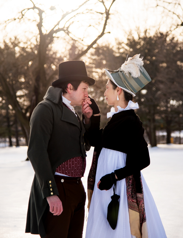 A man kisses his wife's hand while dressed in historical costume during their offbeat engagement at Rose Hill Manor Park in Frederick, Maryland
