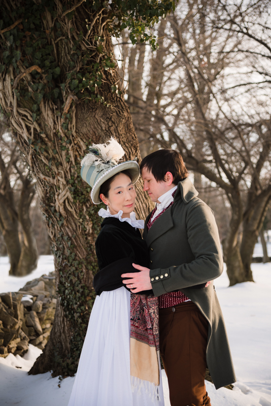 A woman in historical costume poses with her husband on a snowy afternoon during their offbeat engagement at Rose Hill Manor Park
