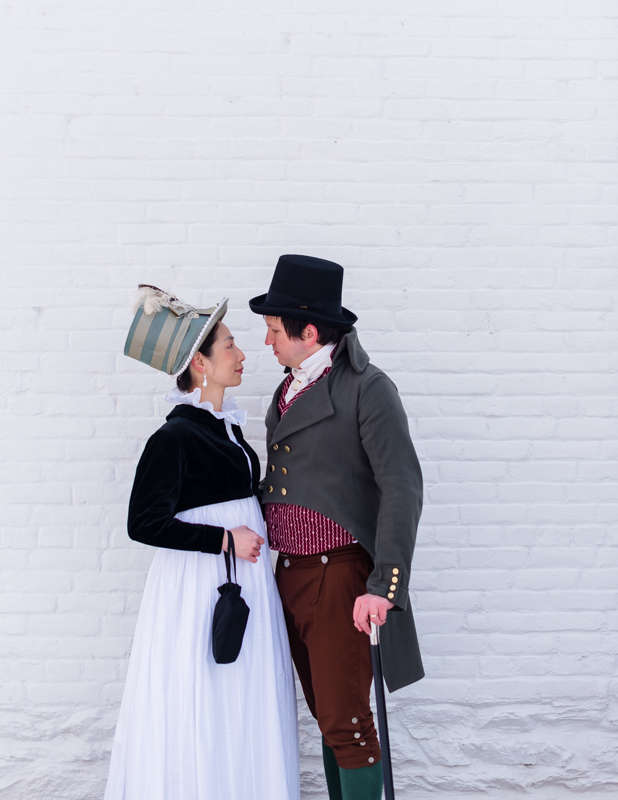 A couple in historical dress smile at each other during their offbeat engagement shoot in Rose Hill Manor Park in Frederick, Maryland