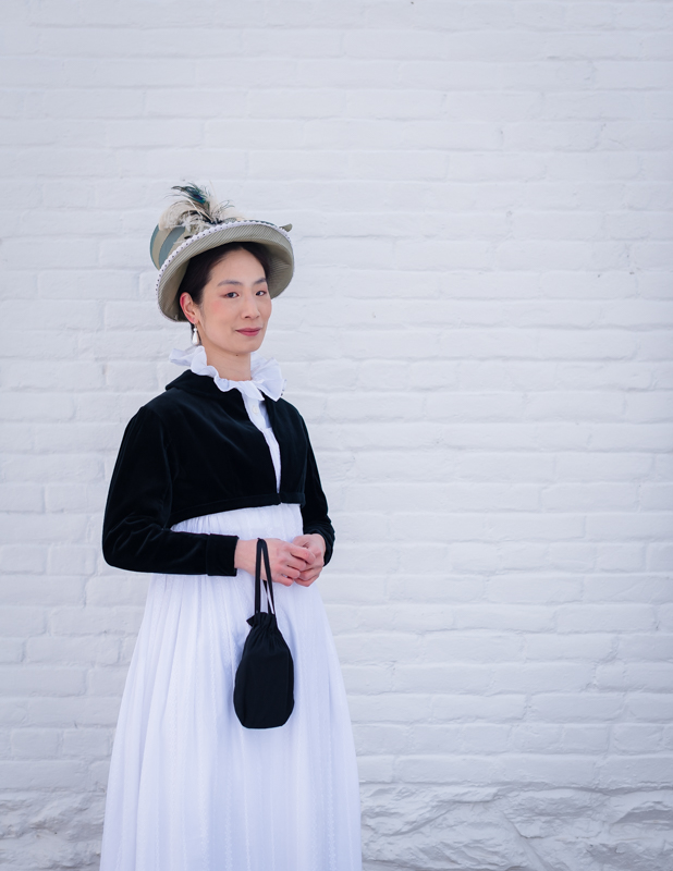 A woman in regency era costume smiles at the camera at Rose Hill Manor Park in Frederick, Maryland