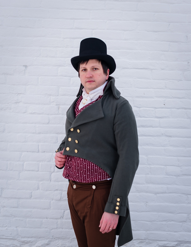 A man in regency era costume looks at the camera at Rose Hill Manor Park in Frederick, Maryland