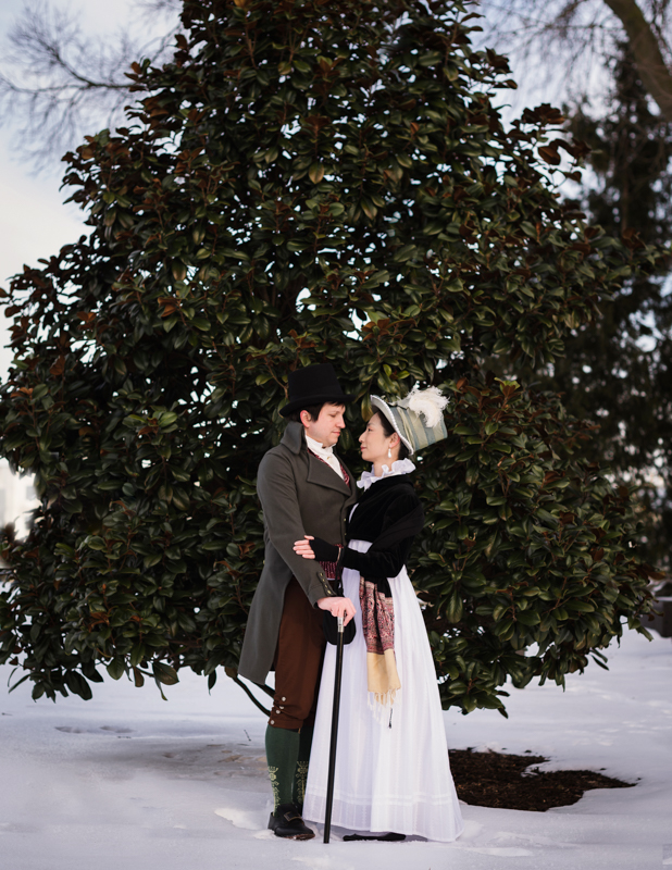 A historical costume couple gaze at each other at Rose Hill Manor Park on a snowy afternoon