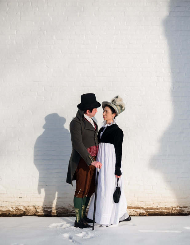 A man in regency era costume smiles down at his wife on a snowy afternoon at Rose Hill Manor Park in Frederick, Maryland