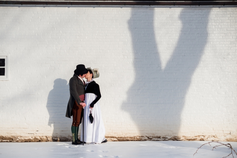 A couple in historical costume kiss during their offbeat engagement shoot in Rose Hill Manor Park in Frederick, Maryland