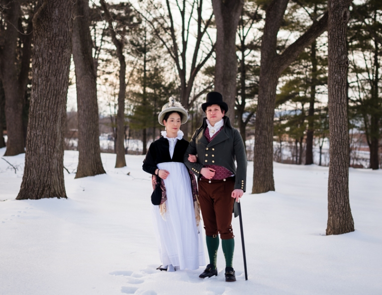 A historical costuming couple stand arm in arm during their offbeat engagement shoot at Rose Hill Manor Park