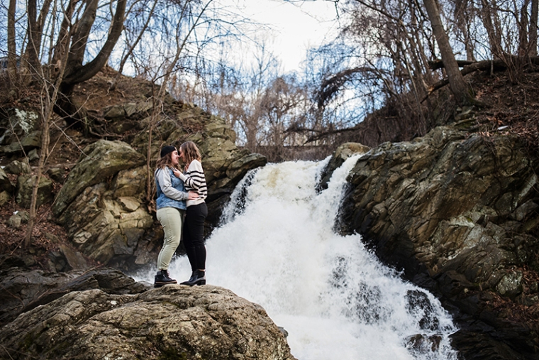 A woman helps her fiancee down from a rock at the base of a waterfall in Harpers Ferry