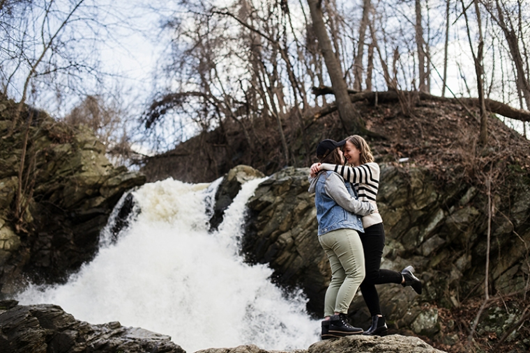 A same-sex couple poses in front of a waterfall in Harpers Ferry