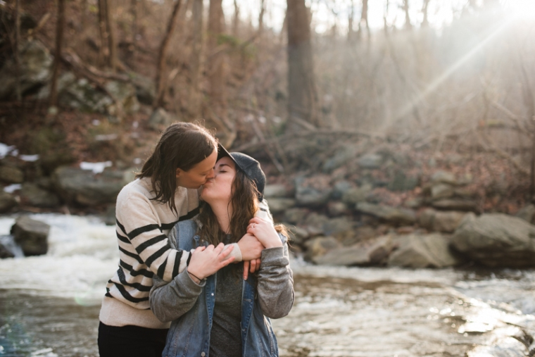 A same-sex couple kisses each other at the base of a waterfall during their engagement photoshoot in Harpers Ferry