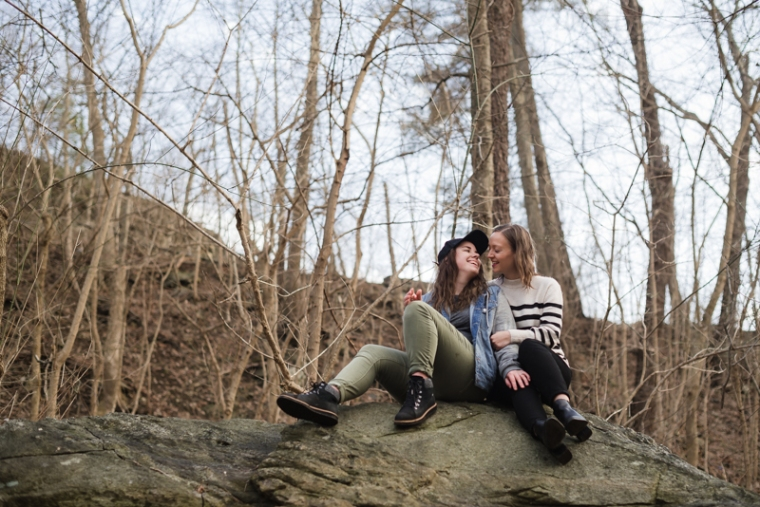 A same-sex couple laughs together during their engagement photos in Harpers Ferry