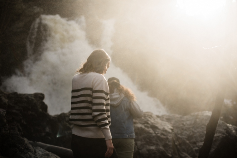 Two woman walk towards a waterfall in Harpers Ferry during their engagement session