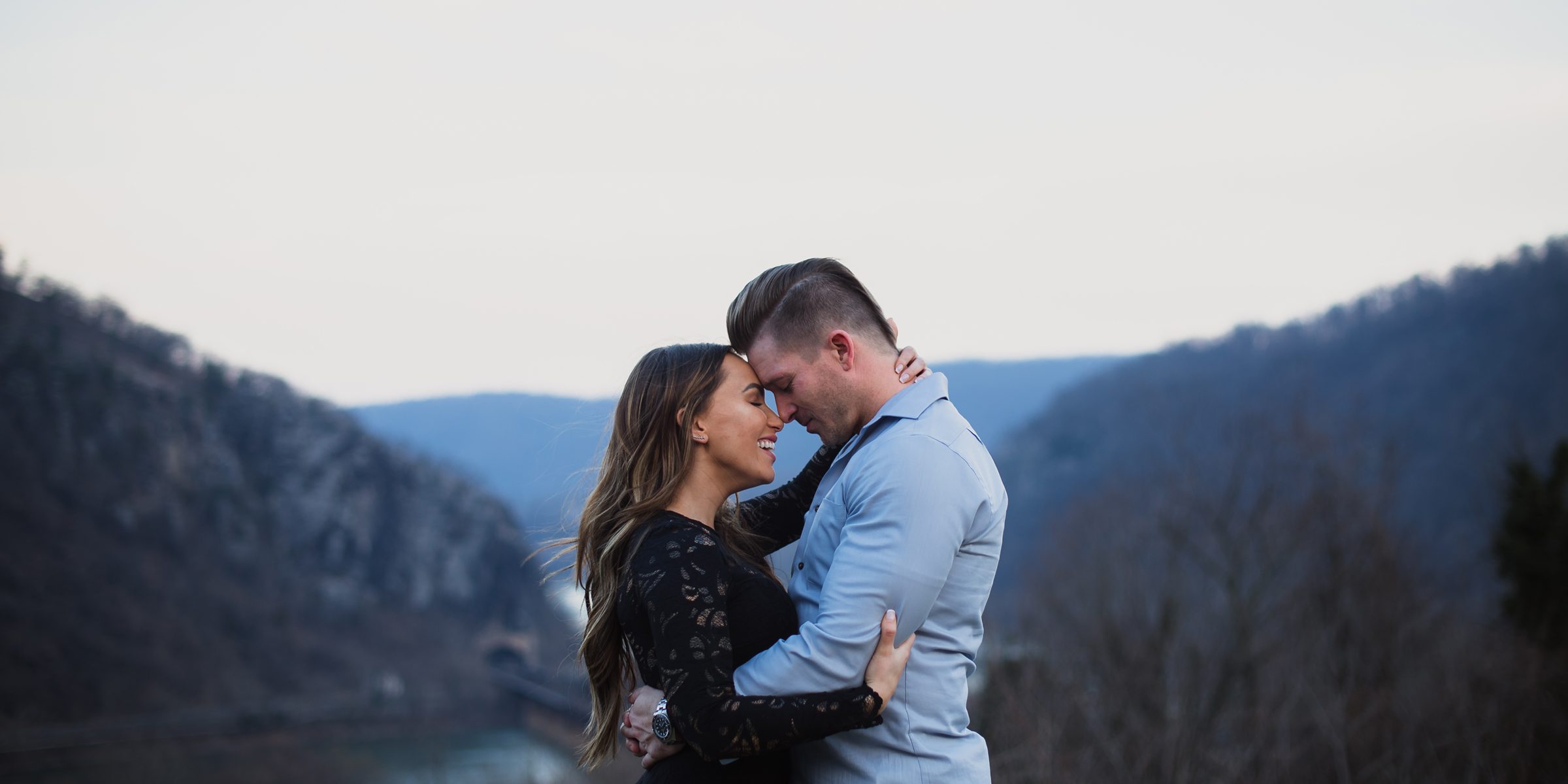 A couple is framed by mountains at an overlook during their Harpers Ferry engagement photos by Jessica Koers West Virginia Wedding Photographer