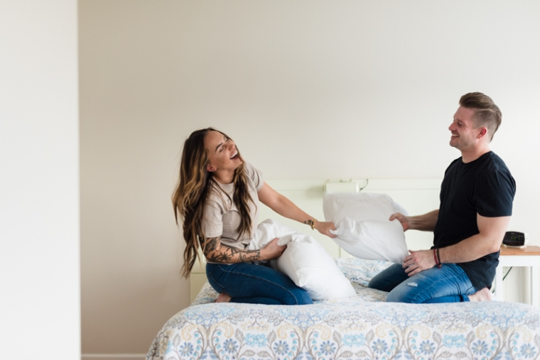 A couple has a pillow fight during their Harpers Ferry engagement photo session