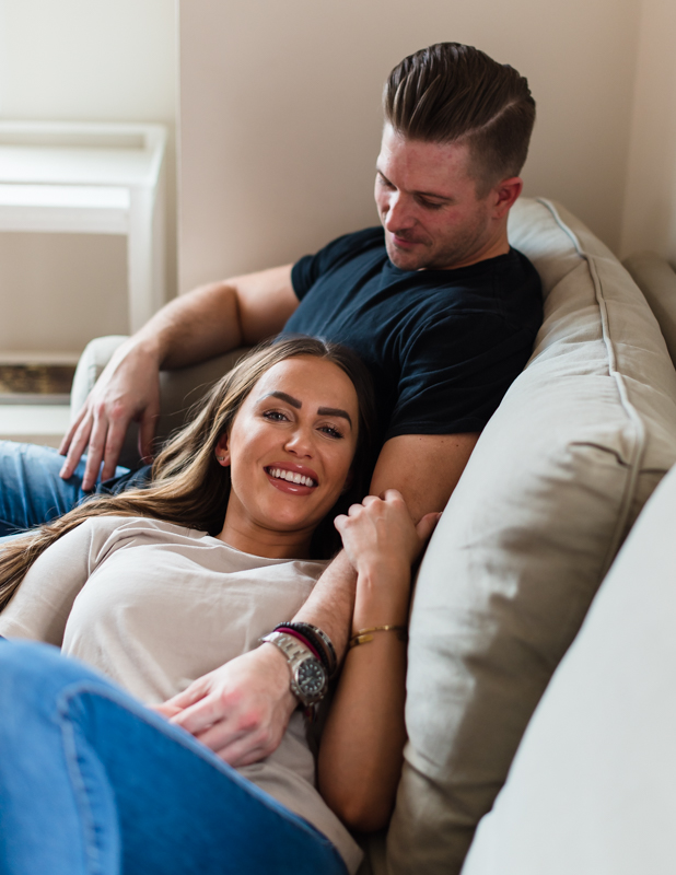 A couple lounges together on a couch in an Airbnb in Harpers Ferry during their engagement shoot